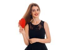 Rozochocona młoda brunetki kobieta z czerwonym sercem w ręk pozować odizolowywam na białym tle Świątobliwy walentynki ` s dnia po Obraz Stock