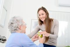 Rozochocona młoda dziewczyna bierze opiekę stara starsza kobieta przy ona do domu obrazy royalty free