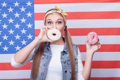 Rozochocona młoda dziewczyna je Amerykańskiego jedzenie Fotografia Stock