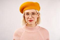 Rozochocona młoda dziewczyna z atrakcyjnym pojawieniem, szeroki uśmiech, ubierający w żółtym berecie, grże menchia dziającego pul obraz stock
