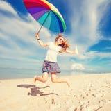 Rozochocona młoda dziewczyna z tęcza parasolem ma Obraz Stock