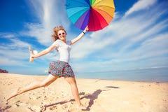 Rozochocona młoda dziewczyna z tęcza parasolem ma Zdjęcie Stock