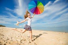 Rozochocona młoda dziewczyna z tęcza parasolem ma Zdjęcia Stock