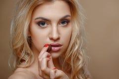 Rozochocona młoda kobieta kusi z słodkim jedzeniem Fotografia Stock