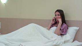 Rozochocona młoda kobieta ma rozmowę telefoniczną na łóżku w sypialni zbiory