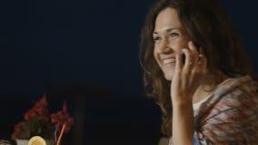 Rozochocona młoda kobieta opowiada nad telefonem kończy wezwanie, uśmiechnięty i roześmiany, zbiory