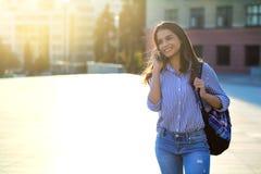 Rozochocona młoda kobieta opowiada telefonem outdoors z światłem słonecznym na jej twarzy i kopii przestrzeni zdjęcia stock