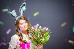 Rozochocona młoda kobieta Patrzeje kamerę z królików ucho, Wielkanocnego jajka koszem i tulipanów kwiatami obraz stock