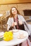 Rozochocona młoda kobieta pije kawę w ulicznej kawiarni obraz royalty free
