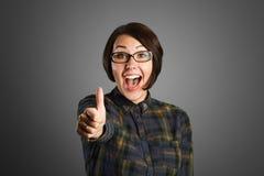 Rozochocona młoda kobieta pokazuje kciuk up podpisuje na popielatym tle zdjęcie stock