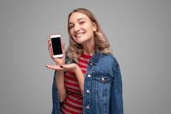 Rozochocona młoda kobieta przedstawia smartphone obraz stock