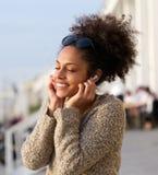 Rozochocona młoda kobieta słucha muzyka outdoors Fotografia Stock