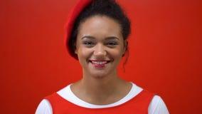 Rozochocona młoda kobieta szczerze uśmiecha się pozować przy kamerą, odosobniony czerwony tło zdjęcie wideo