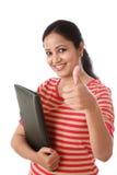 Rozochocona młoda kobieta trzyma falcówkę i robi kciukowi w górę gestur zdjęcie royalty free