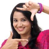 Rozochocona młoda kobieta tworzy ramę z palcami obraz royalty free