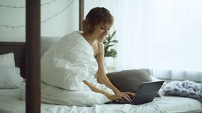 Rozochocona młoda kobieta używa jej laptopu obsiadanie w łóżku w domu Obraz Stock