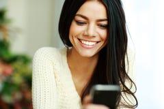 Rozochocona młoda kobieta używa jej smartphone Fotografia Royalty Free
