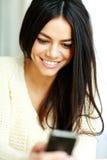 Rozochocona młoda kobieta używa jej smartphone Obrazy Royalty Free