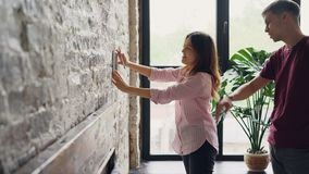 Rozochocona młoda kobieta wybiera miejsce szczęśliwego dla obramiającej fotografii na ściana z cegieł, podczas gdy jej mąż pomaga zbiory