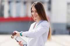 Rozochocona młoda piękna kobieta wewnątrz w błękitnej koszula utrzymuje jej touchpad z uśmiechem i spojrzeniami przy jego zegarek Obrazy Stock