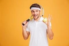 Rozochocona młodego człowieka gracz w tenisa mienia piłka i kant obrazy stock