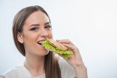 Rozochocona młoda dziewczyna jest zjadliwym niezdrowym jedzeniem Obraz Royalty Free