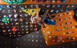 Rozochocona młoda kobieta bouldering w wspinaczkowym gym Zdjęcie Royalty Free