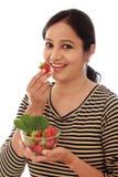Rozochocona młoda kobieta trzyma puchar truskawki Fotografia Royalty Free