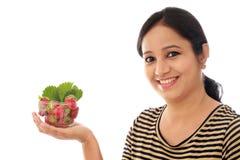 Rozochocona młoda kobieta trzyma puchar truskawki Zdjęcia Stock