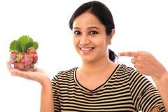 Rozochocona młoda kobieta trzyma puchar truskawki Obrazy Royalty Free