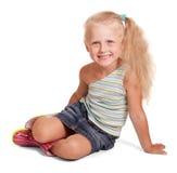 Rozochocona mała blondynki dziewczyna w spódnicy i bluzki obsiadaniu odizolowywającym Obrazy Royalty Free