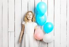 Rozochocona mała blondynki dziewczyna z balonami na białym drewnianym backgrou Zdjęcia Royalty Free