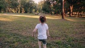 Rozochocona mała dziewczynka biega zdala od kamery w parku na pogodnym letnim dniu Tylny widok, wolny mo zbiory wideo
