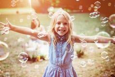 Rozochocona mała dziewczynka cieszy się bąbla dmuchanie obrazy stock