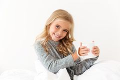 Rozochocona mała dziewczynka trzyma filiżankę trójnik, patrzeje kamerę podczas gdy obrazy stock