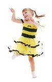 Rozochocona mała dziewczynka w żółtym smokingowym doskakiwaniu i obrazy stock