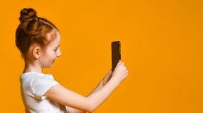 Rozochocona mała miedzianowłosa dziewczyna bierze selfie z telefonem komórkowym przeciw żółtej ścianie zdjęcie stock