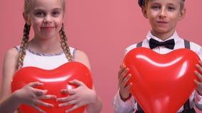 Rozochocona mała para trzyma sercowatych balony i ono uśmiecha się kamera, miłość zdjęcie wideo
