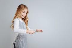 Rozochocona małej dziewczynki pozycja odizolowywająca na popielatym tle fotografia stock