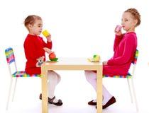 Rozochocona małej dziewczynki sztuka w restauraci z zdjęcie stock