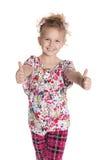 Rozochocona mała dziewczynka trzyma jej aprobaty Fotografia Stock