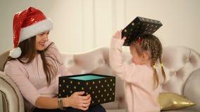 Rozochocona mama i jej śliczny córki dziecko otwieramy prezent Rodzic i małe dziecko ma zabawę blisko choinki indoors zbiory