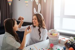 Rozochocona matka i córka przygotowywamy dla wielkanocy Trzymają czekoladowych jajka i uśmiech Dekoracja na stole Wzorcowa odzież zdjęcia stock