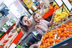 Rozochocona matka i mała dziewczynka wybiera świeże owoc Obraz Stock
