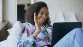 Rozochocona mieszana biegowa dziewczyna ma wideo gadkę z przyjaciółmi używa laptop kamerę podczas gdy kłamający na łóżku Fotografia Stock