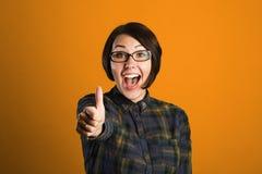 Rozochocona młoda kobieta pokazuje kciuk up podpisuje na pomarańczowym tle Zdjęcie Royalty Free