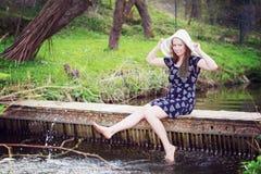 Rozochocona modna kobieta siedzi na małym mosta i chełbotania wa Fotografia Royalty Free