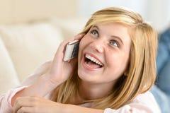 Rozochocona nastoletnia kobieta śmia się dzwonić na telefonie Fotografia Royalty Free