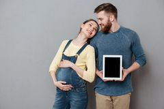 Rozochocona para oczekuje dziecka i pokazuje pustego pastylka ekran komputerowego zdjęcie royalty free