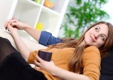 Rozochocona para relaksuje wpólnie na kanapie w żywym pokoju Zdjęcie Stock